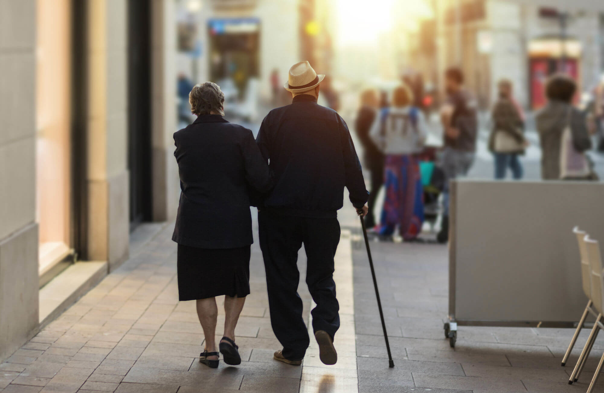An older couple walking down a city sidewalk