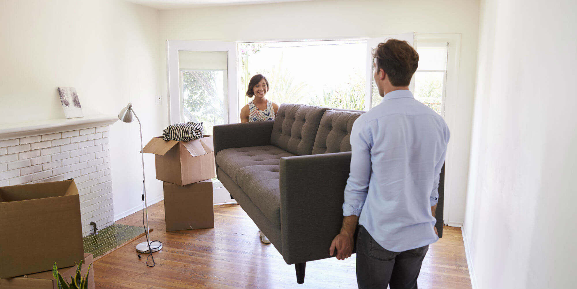 Couple moving a couch into their new home